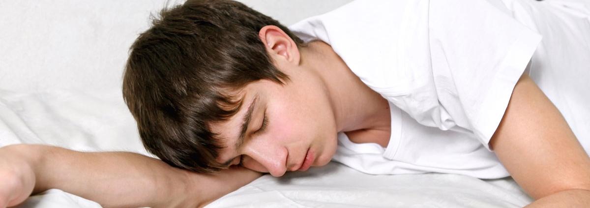 Teenager sover i sin seng